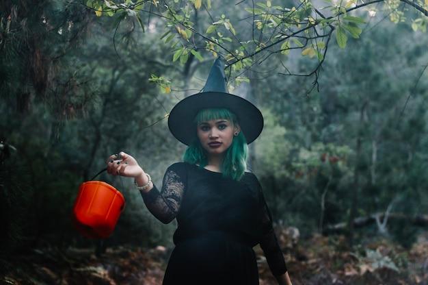 Девушка ведьмы с ведром в лесу