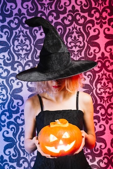 Witch girl with lighted pumpkin