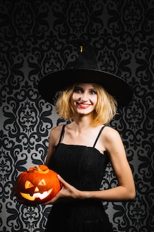 Witch girl with pumpkin smiling at camera