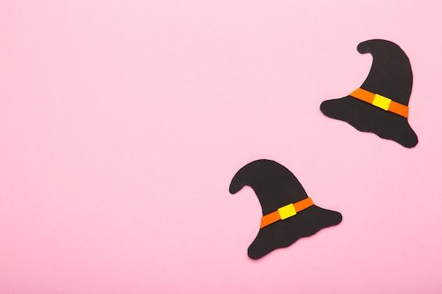 ピンクの背景の魔女の帽子。コピースペースとピンクの背景のハロウィーンの紙の装飾。