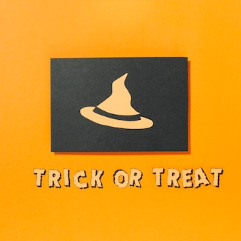 Witch hat on piece of black paper with trick or treat inscription