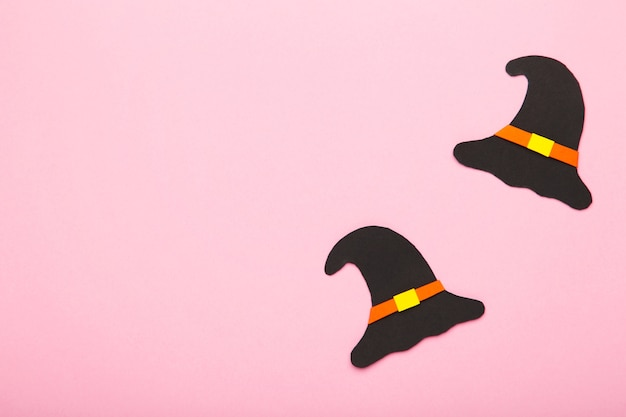 Witch hat on pink background. halloween paper decorations on pink background with copy space.
