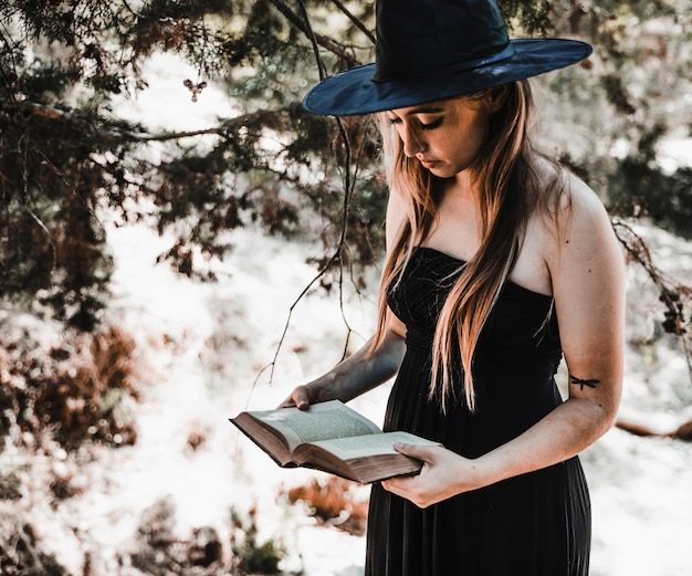 Witch in hat reading aged book in forest daytime