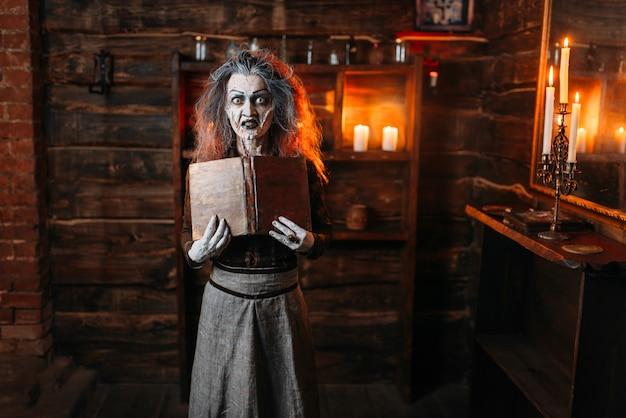 Ведьма держит книгу заклинаний, темные силы колдовства