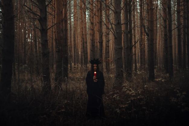 검은 의상을 입은 마녀가 어둡고 우울한 숲에서 촛불을 들고 있다