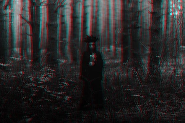 검은 의상을 입은 마녀는 촛불로 어둠의 주문을 수행합니다. 3d 글리치 가상 현실 효과가 있는 흑백