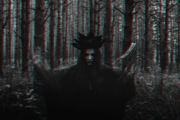 Ведьма в черном костюме исполняет темные заклинания со свечами в лесу. размытое фото с размытием из-за большой выдержки. черно-белый с эффектом виртуальной реальности 3d глюк