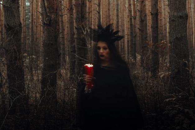 검은 의상을 입은 마녀는 숲에서 촛불로 어두운 주문을 수행합니다. 노출 시간이 길어 흐릿한 사진
