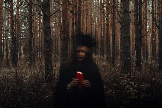 검은 의상을 입은 마녀가 양초를 손에 들고 어두운 숲에서 신비로운 의식과 신비로운 주문을 수행합니다. 장시간 노출로 인해 흐릿한 사진
