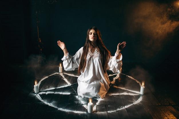 五芒星の円の中心に座っている白いシャツの魔女、キャンドル、オカルトの儀式、精霊の喚起。神秘主義と悪魔払い