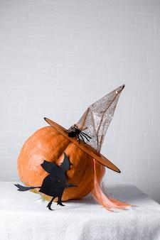 魔女の帽子をかぶったオレンジ色のカボチャを持つ黒い紙のdiyの魔女