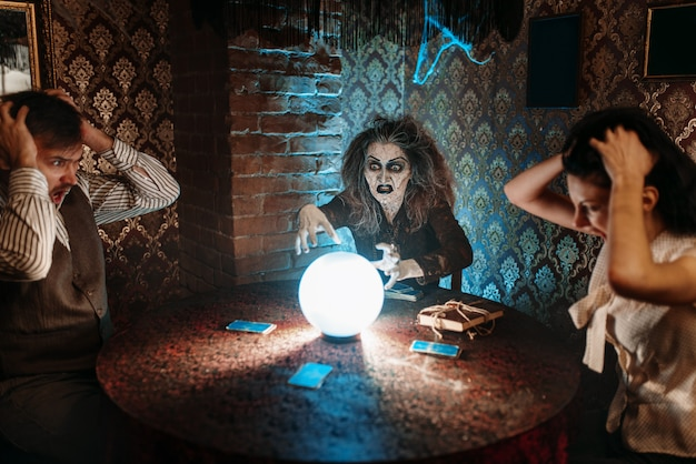 Witch reads scary magic spell over a crystal ball, young people in horror on spiritual seance. female foreteller calls the spirits