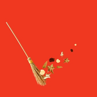 A witch's broom cleaning the leaves on the red background. halloween autumn concept. large copy space