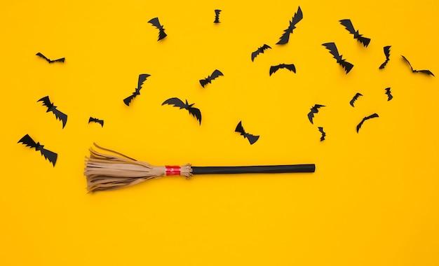 마녀의 빗자루, 노란색 배경에 날아다니는 박쥐. 할로윈 수제 장식. 평면도. 플랫 레이
