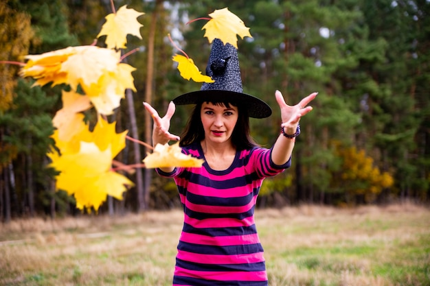Witch throws leaves in the autumn forest halloween costume party magician