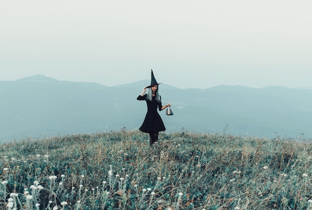 Witch walking on autumn meadow