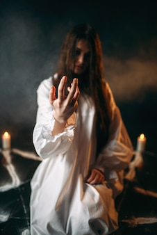 Witch in white shirt calls upon the spirits, pentagram circle with candles, dark magic ritual process, witchcraft. occultism and exorcism