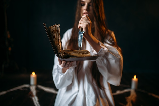 Witch in white shirt holds knife and reads spell, pentagram circle with candles, dark magic ritual process. occultism and exorcism
