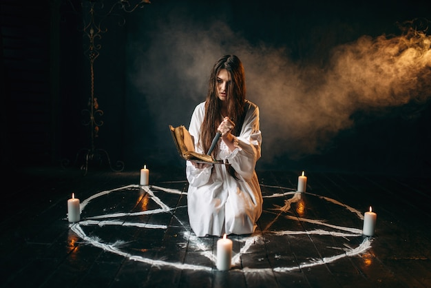 Witch in white shirt holds knife and reads spell