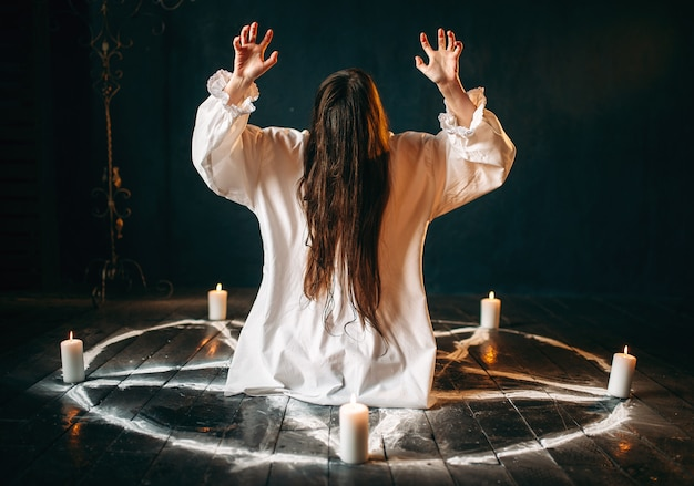 Witch in white shirt produses occult ritual in pentagram circle with candles. dark magic ritual, occultism and exorcism