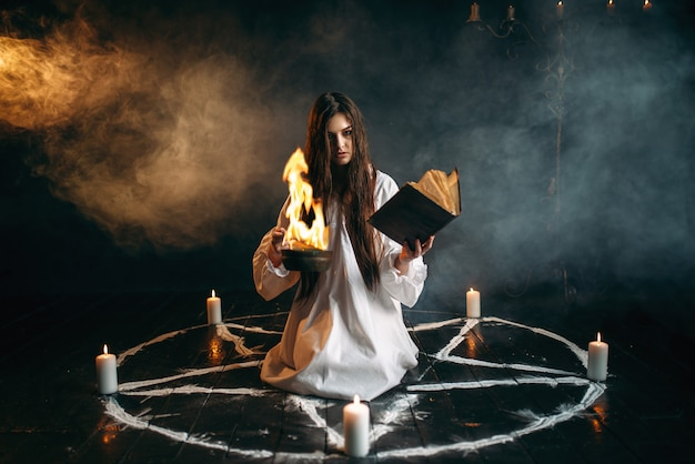 Witch in white shirt sitting in the center of pentagram circle with candles, dark magic ritual process. occultism and exorcism