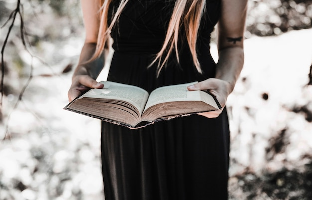Witch with aged book in sunny forest