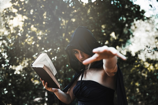 Witch with spellbook using magic in sunlit woods