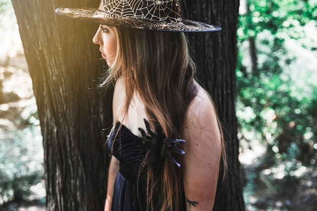 Witch with spider on chest in forest daytime