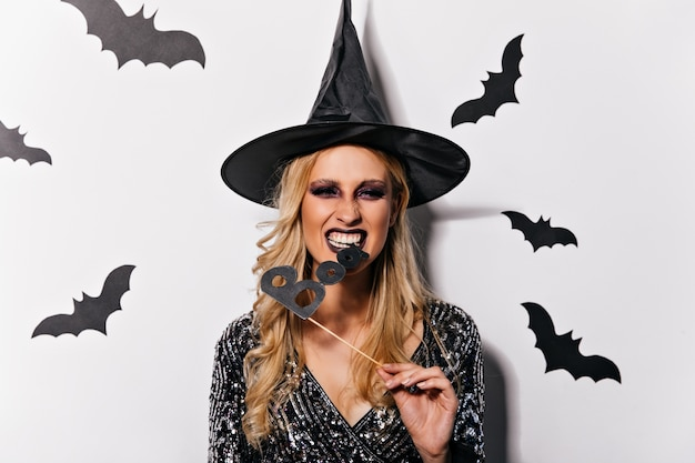 Strega con acconciatura ondulata che celebra halloween. vampiro femminile estatico in cappello divertente che posa con i pipistrelli.