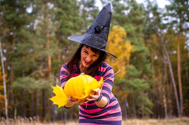 Witch woman holding pumpkin with scary emotions in autumn forest. close up