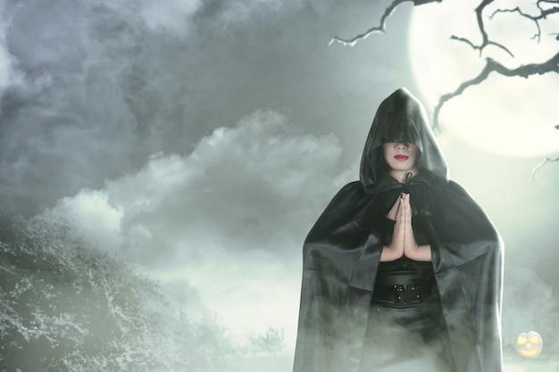 Ведьма женщина в черном с капюшоном делает ритуал магии