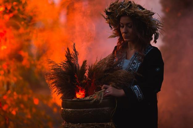 魔女の女性が森の大釜で呪文を作る