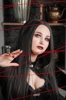 요술, 마법. 할로윈 이야기는 아름다운 젊은 섹시한 마녀가 빨간 실을 통해 요술을 부리는 것입니다. 중세의 마법사가 운명의 실을 자릅니다.