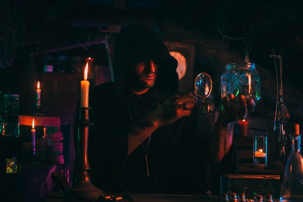 Witcher alchemist makes a secret potion in gloomy laboratory workshop. dark magician sorcerer in halloween costume at table