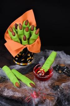 アーモンドの指の爪が付いたショートクラストペストリーで作られた魔女の指のクッキー。ハッピーハロウィンパーティーに最適