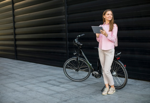 Молодая женщина witg цифровая таблетка и электрический велосипед напольные