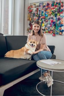 С собакой. владелец женского питомца сидит на диване со своей собакой