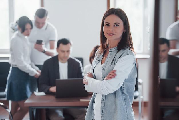 腕を組んで。昼間の近代的な教室でのビジネス会議での人々のグループ