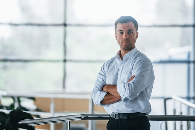 腕を組んで。ビジネスマンの肖像画。自信のあるマネージャーがオフィスに立っています。