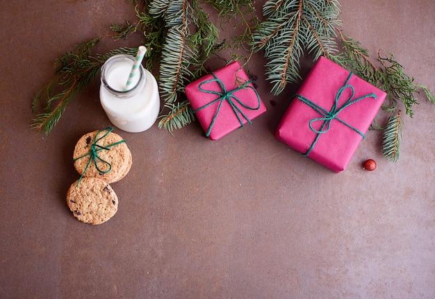 焼きたてのクッキー、牛乳、ギフト、クリスマスツリーのおもちゃ、クリスマスツリーの小枝、上からの眺め。テキストの場所。フラットレイ