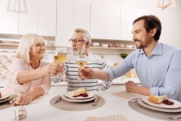 ご両親のご多幸をお祈り申し上げます。シャンパンと笑顔でいっぱいのメガネを上げながら、夕食を食べて、彼の年老いた両親と一緒に休日を楽しんでいるポジティブな幸せな成熟した男
