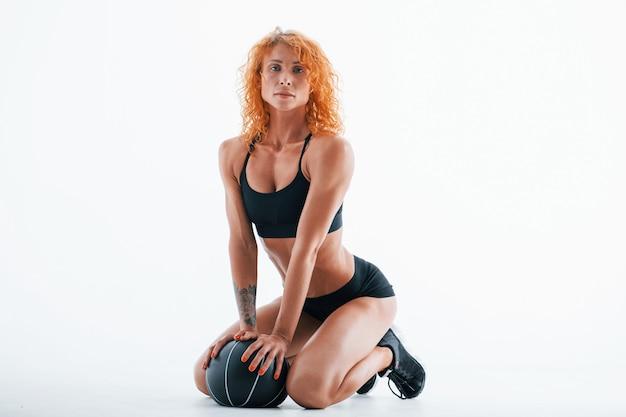 검은 색 축구 공. 빨간 머리 여성 보디 빌더는 흰색 공간에 스튜디오에 있습니다.