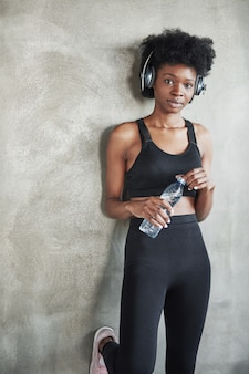 With bottle of fresh water. portrait of african american girl in fitness clothes having a break after workout