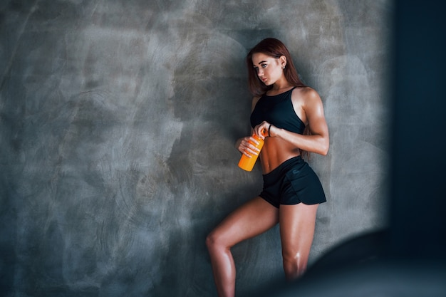 With bottle of water. young fitness woman with slim type of body and in black sportive clothes is in the gym.
