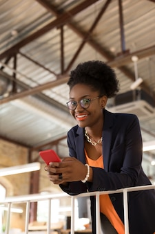 With bright lips. dark-skinned stylish young woman with bright lips holding her smartphone