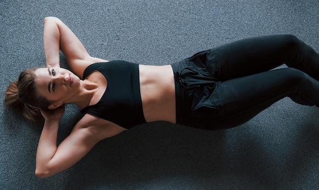 깨끗한 피부로. 체육관 바닥에서 복근을한다. 아름 다운 여성 피트 니스 여자입니다.