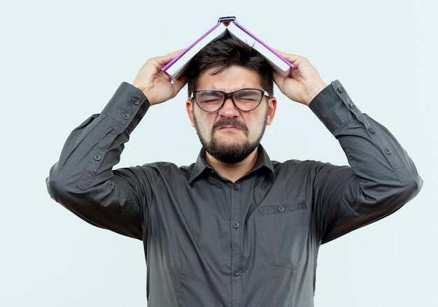 Con gli occhi chiusi il giovane uomo d'affari arrabbiato con gli occhiali ha coperto la testa con il libro isolato su bianco