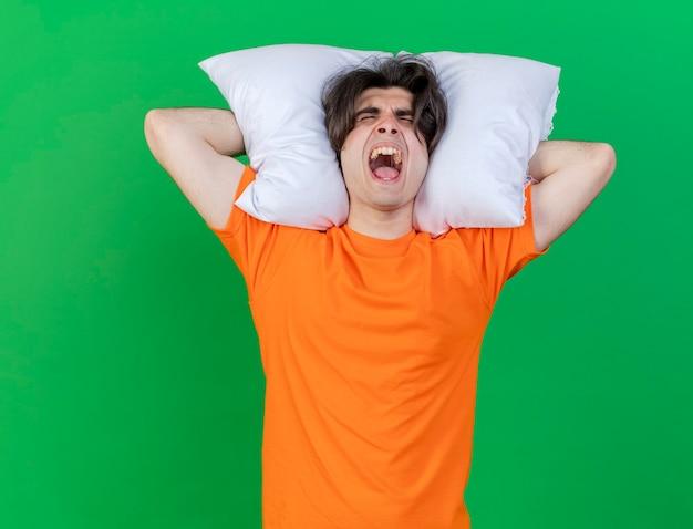 緑の背景に分離された頭の後ろに枕を保持している怒っている若い病気の人の目を閉じて
