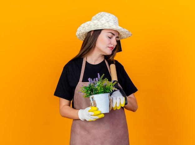 Con gli occhi chiusi bella ragazza giardiniere che indossa uniforme e cappello da giardinaggio