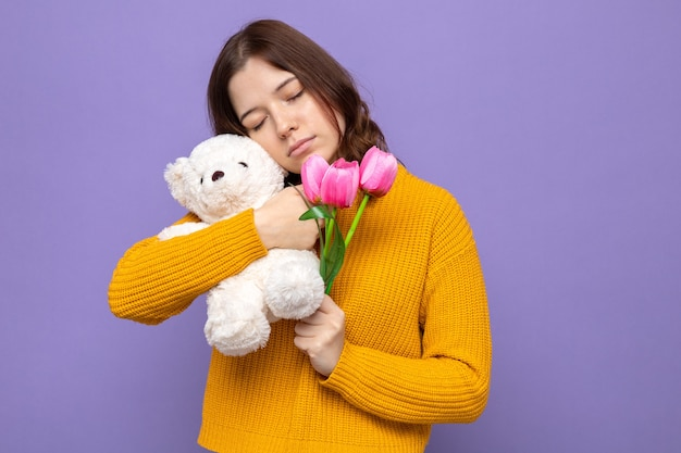 With closed eyes beautiful young girl holding flowers with teddy bear